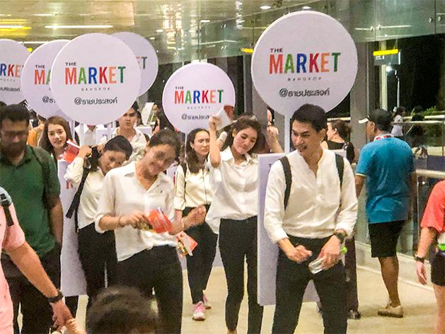 「The Market Bangkok」のサインを背負って歩く集団